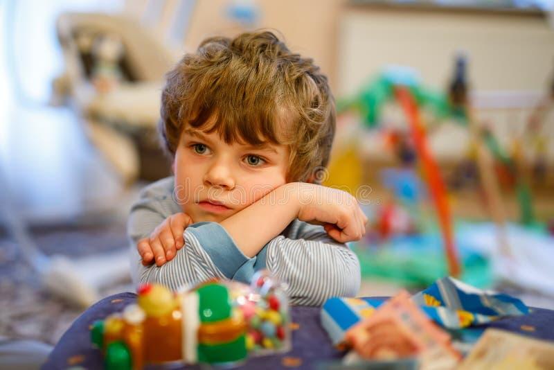 Portret van weinig jong geitjejongen droevig op verjaardag kind met veel stuk speelgoed stock foto's