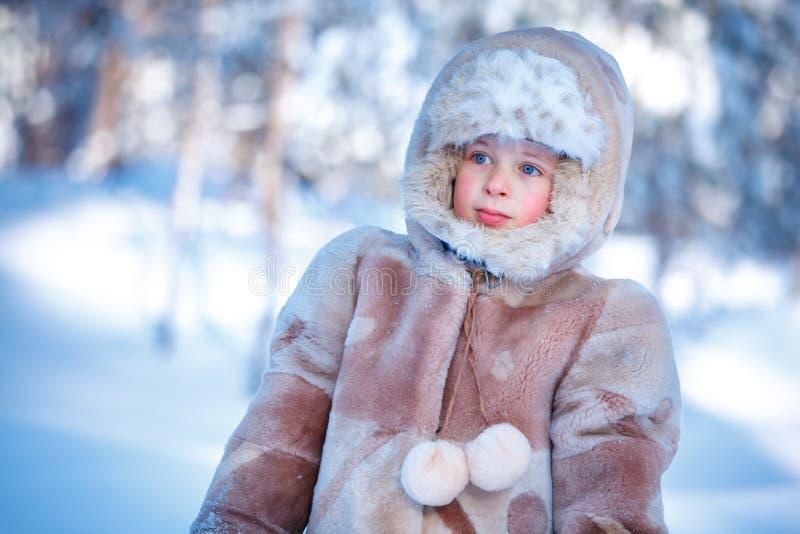 Portret van weinig jongen die in openlucht in de winterbos spelen royalty-vrije stock foto