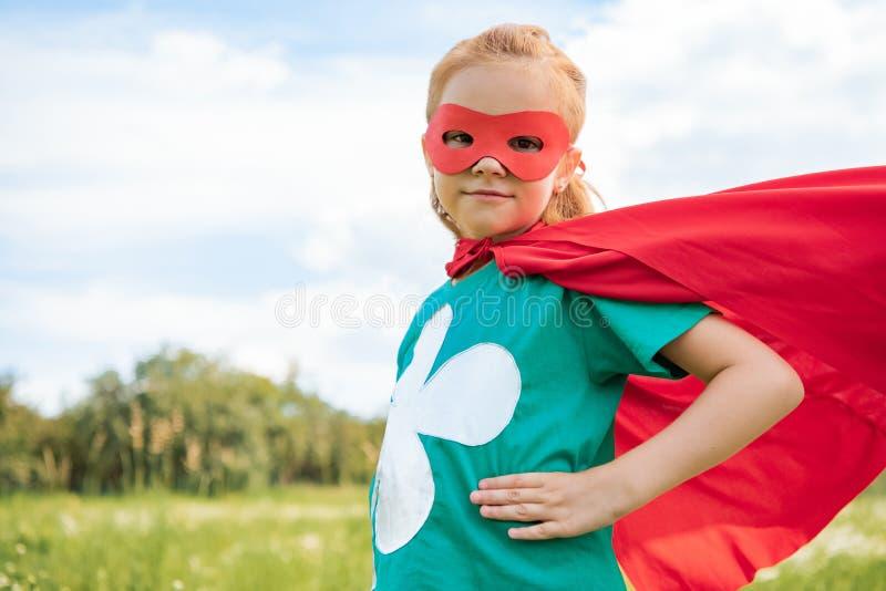 portret van weinig kind in rood superherokostuum die zich met de handen in de zij bevinden stock afbeelding