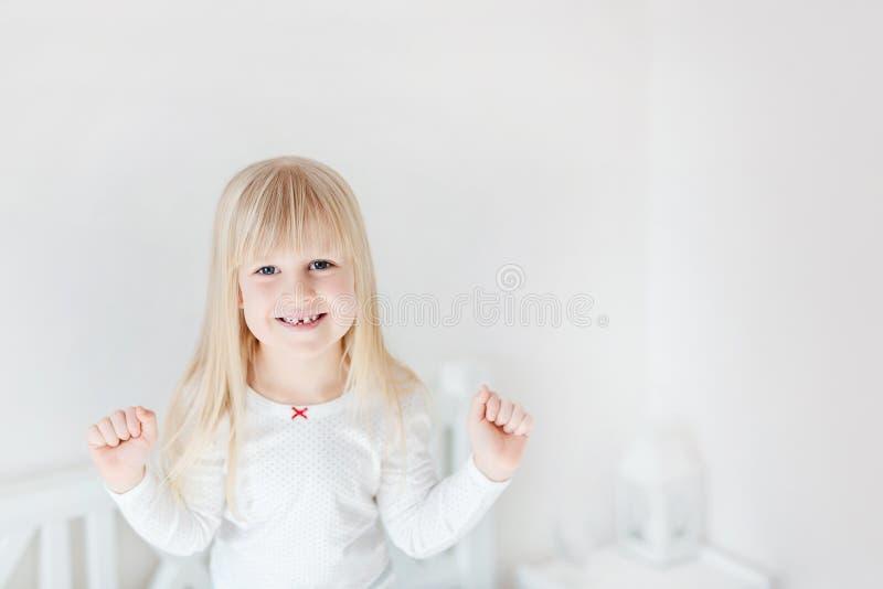 Portret van weinig leuk meisje die zich op bed bevinden Aanbiddelijk glimlachend kind Blond jong geitje die op vuisten opheffen K royalty-vrije stock foto's