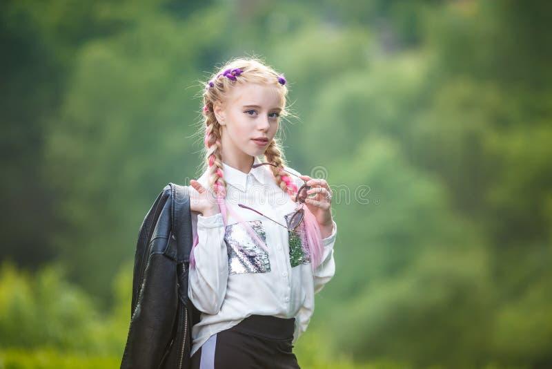 Portret van weinig mooi modieus jong geitjemeisje op groene bosachtergrond stock fotografie