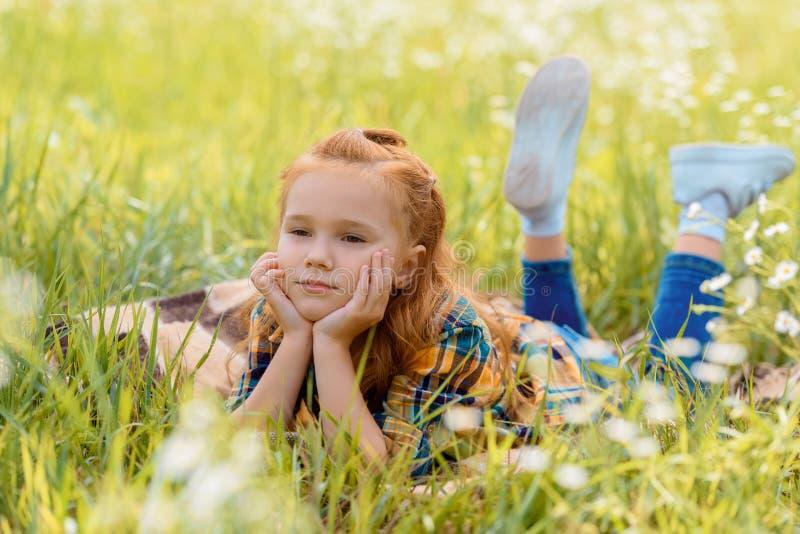 portret van weinig peinzend kind die op groen gras rusten royalty-vrije stock foto