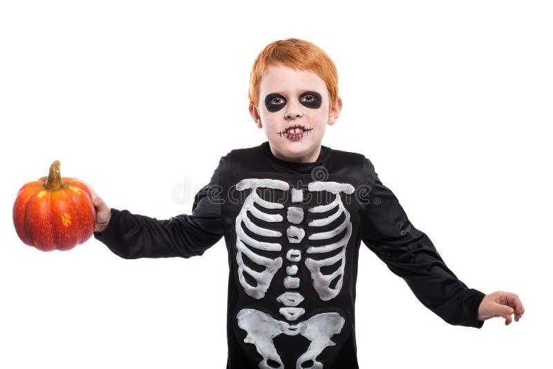 Portret van weinig rode haired jongen die Halloween-skeletkostuum dragen en pompoen houden stock foto