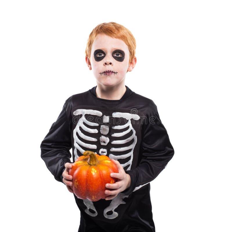 Portret van weinig rode haired jongen die Halloween-skeletkostuum dragen en pompoen houden stock afbeelding
