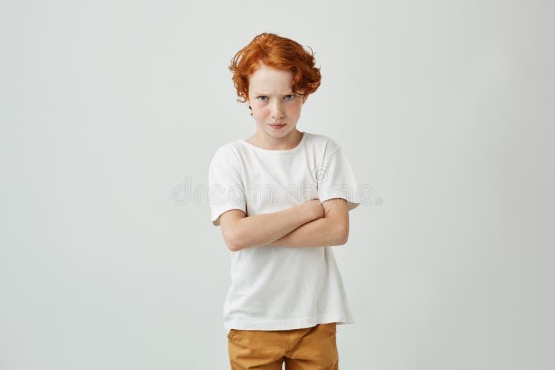 Portret van weinig rode haired jongen die met leuke sproeten in witte t-shirt in camera met beledigde uitdrukking wanneer van hem royalty-vrije stock afbeelding