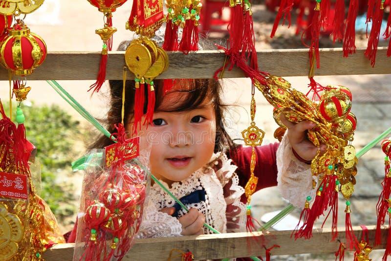 Portret van weinig Vietnamees meisje in rode kleding met traditionele Vietnamese Nieuwjaardecoratie op de straat van stad stock afbeelding