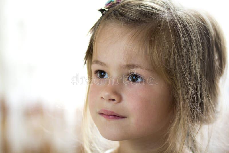 Portret van weinig vrij jong kindmeisje met grijze ogen en klem in verspreid fijn blond haar die dreamily in afstand op bl kijken stock foto