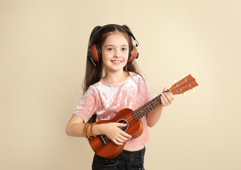 Portret van weinig vrolijk meisje die met hoofdtelefoons gitaar spelen royalty-vrije stock afbeelding