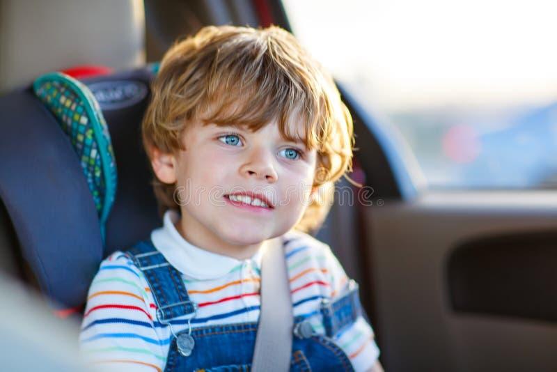 Portret van weinig zitting van de jong geitjejongen in de zetel van de veiligheidsauto stock afbeeldingen