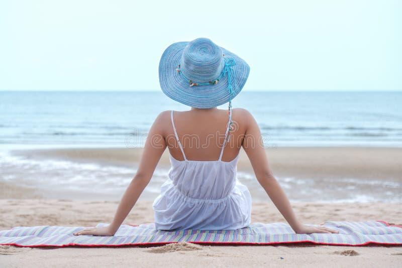 Portret van wijfje met hoed het ontspannen op strandmat door strand royalty-vrije stock foto