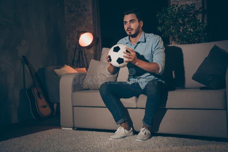 Portret van z'n aardige verslaafde zenuwjongen die op divan zit te kijken naar sportshow die in handen houdt stock foto