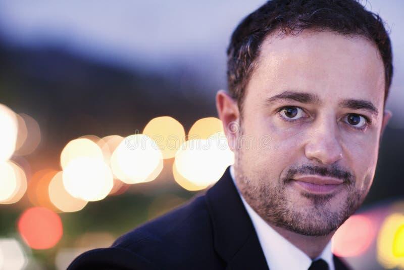 Portret van zakenman bij schemer met vage lichten op de achtergrond, in openlucht in de stad, close-up royalty-vrije stock afbeeldingen