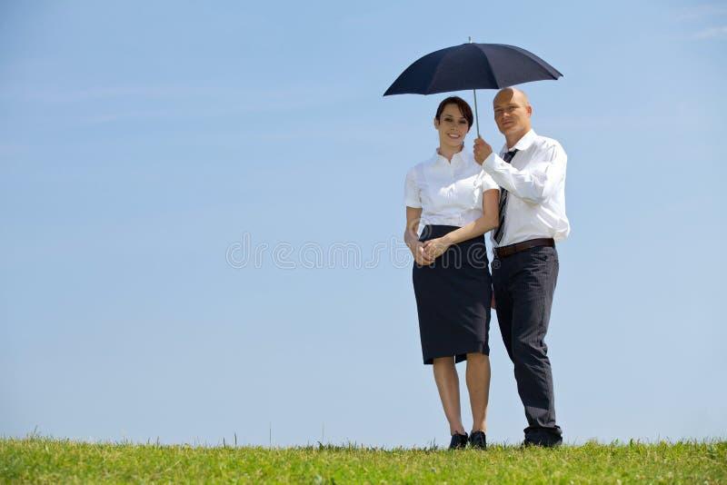Portret van zakenman en onderneemster onder paraplu in park royalty-vrije stock afbeeldingen