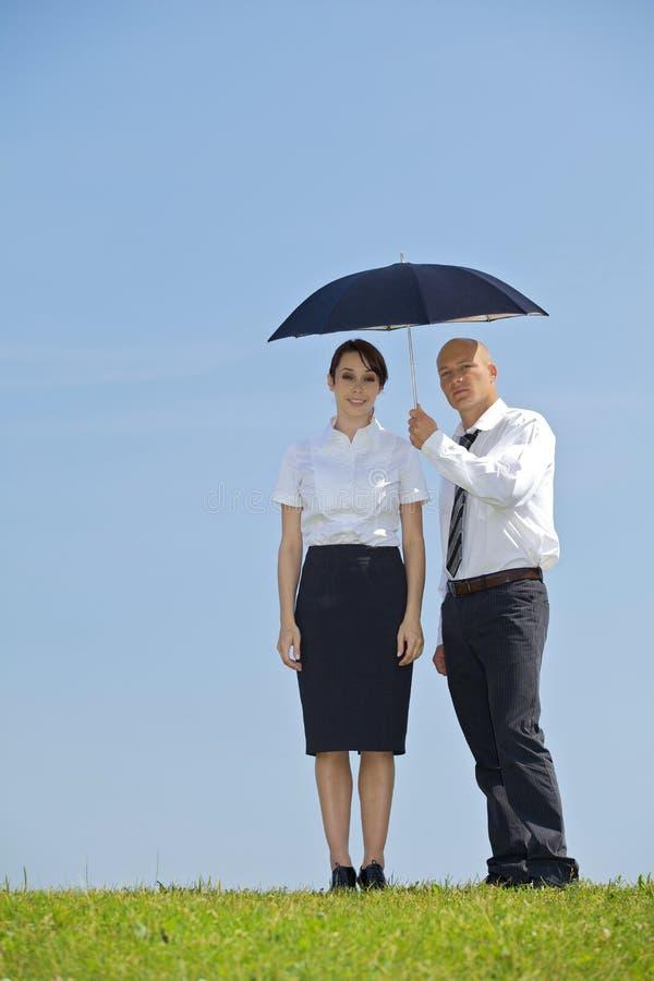 Portret van zakenman en onderneemster onder paraplu in park royalty-vrije stock fotografie