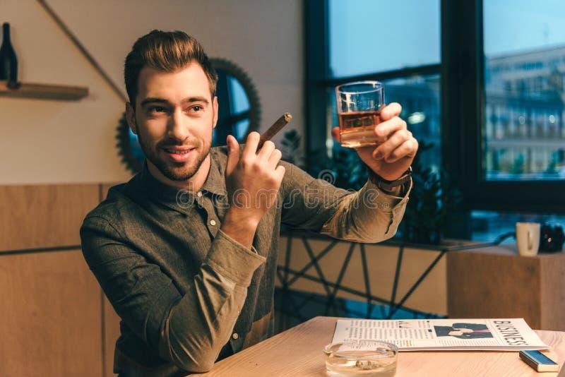 portret van zakenman met het glas van de sigarenholding cognac stock foto