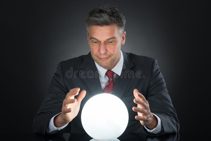 Portret van Zakenman Predicting Future With Crystal Ball stock foto