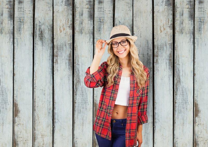 Portret van zeker wijfje die hipster zich tegen houten muur bevinden stock afbeelding