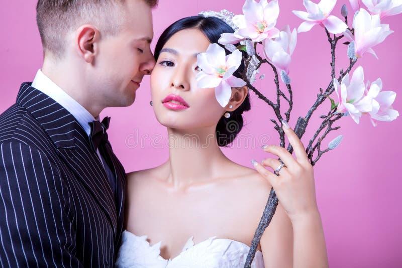 Portret van zekere bruid met het houden van van bruidegom tegen roze achtergrond royalty-vrije stock foto's