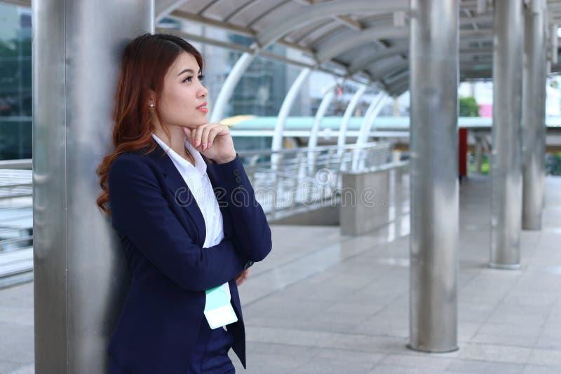 Portret van zekere jonge Aziatische onderneemster die zich bij stoep bevinden en ver weg bekijken bij Het denken en de nadenkende stock foto's