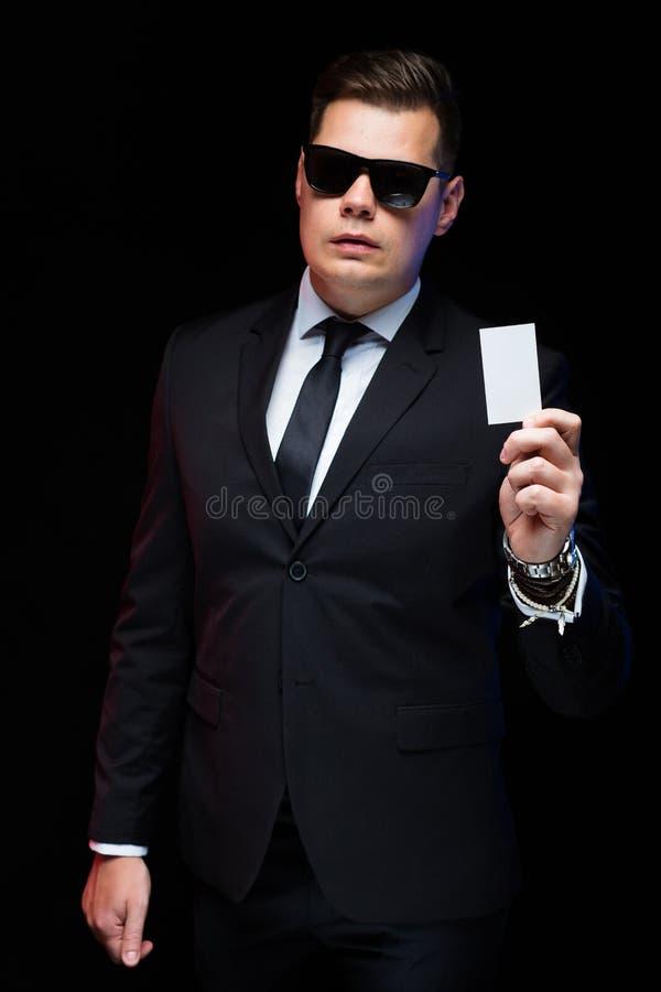 Portret van zekere knappe elegante zakenman die in zonnebril visitekaartje in zijn hand op zwarte achtergrond houden stock foto's