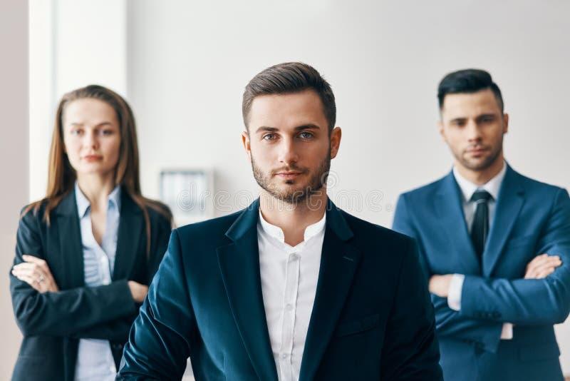 Portret van zekere knappe zakenman in bureau met zijn team op achtergrond royalty-vrije stock fotografie