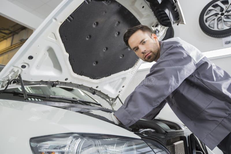 Portret van zekere mannelijke reparatiearbeider die motor van een auto in reparatiewerkplaats herstellen royalty-vrije stock fotografie