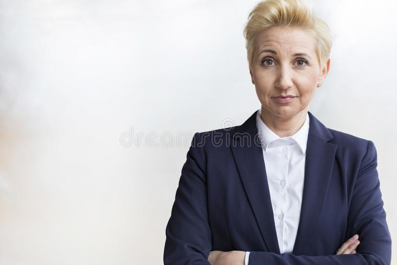 Portret van zekere rijpe blonde onderneemster in blauw kostuum die zich met die wapens bevinden tegen witte muur op kantoor worde royalty-vrije stock afbeelding