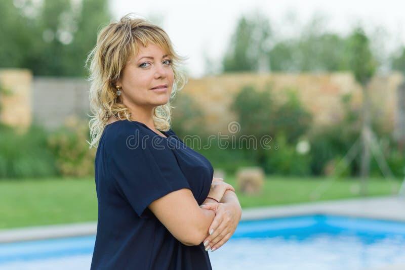 Portret van zekere succesvolle rijpe vrouw met gekruiste wapens De achtergrond van pool, privé woonplaats, wijfje onderzoekt kwam stock fotografie