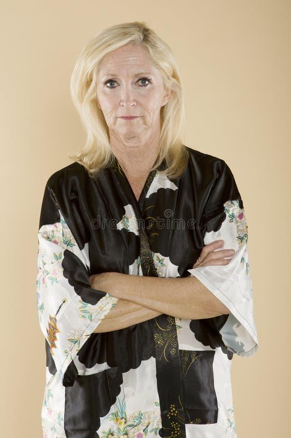 Portret van zekere vrouw op middelbare leeftijd met gekruiste wapens stock afbeeldingen