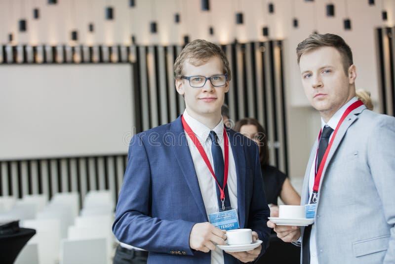 Portret van zekere zakenlieden die koffiekoppen in overeenkomstcentrum houden royalty-vrije stock foto's