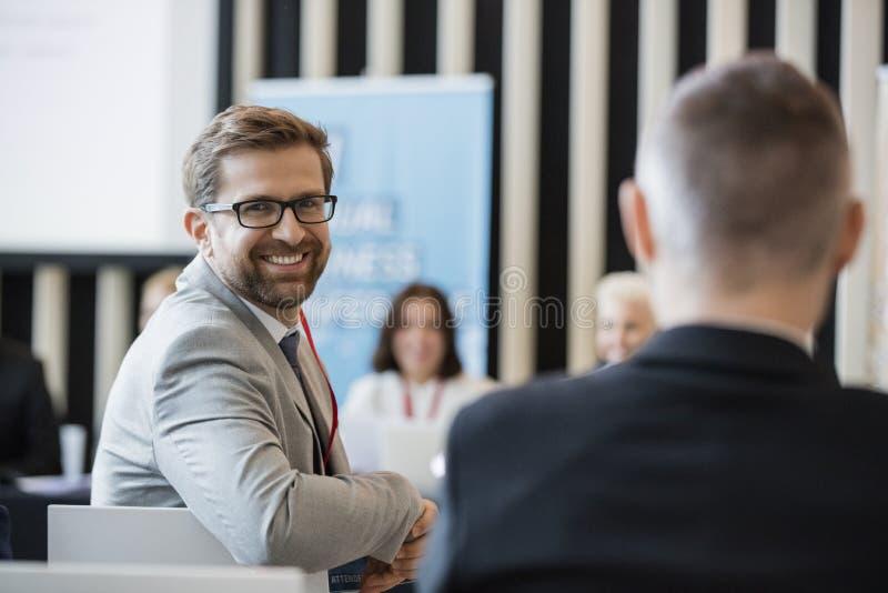 Portret van zekere zakenmanzitting in seminariezaal stock foto's
