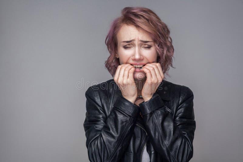 Portret van zenuwachtig meisje met kort kapsel en make-up in het toevallige jasje die van het stijl zwarte leer bijtend haar spij royalty-vrije stock afbeelding