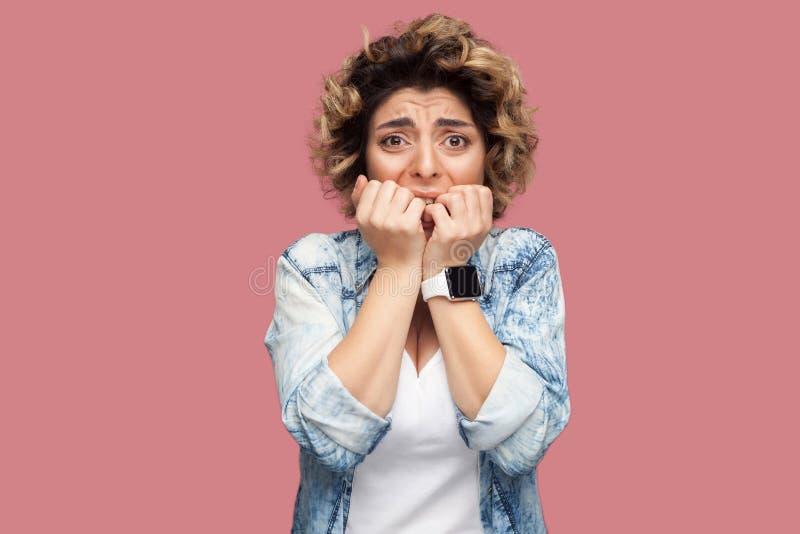 Portret van zenuwachtige jonge vrouw met krullend kapsel in toevallig blauw overhemd die, haar spijkers bitting en camera bekijke royalty-vrije stock foto