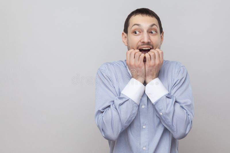 Portret van zenuwachtige knappe varkenshaarzakenman in klassiek lichtblauw, zijn spijkers bitting en overhemd die weg eruit zien  stock fotografie