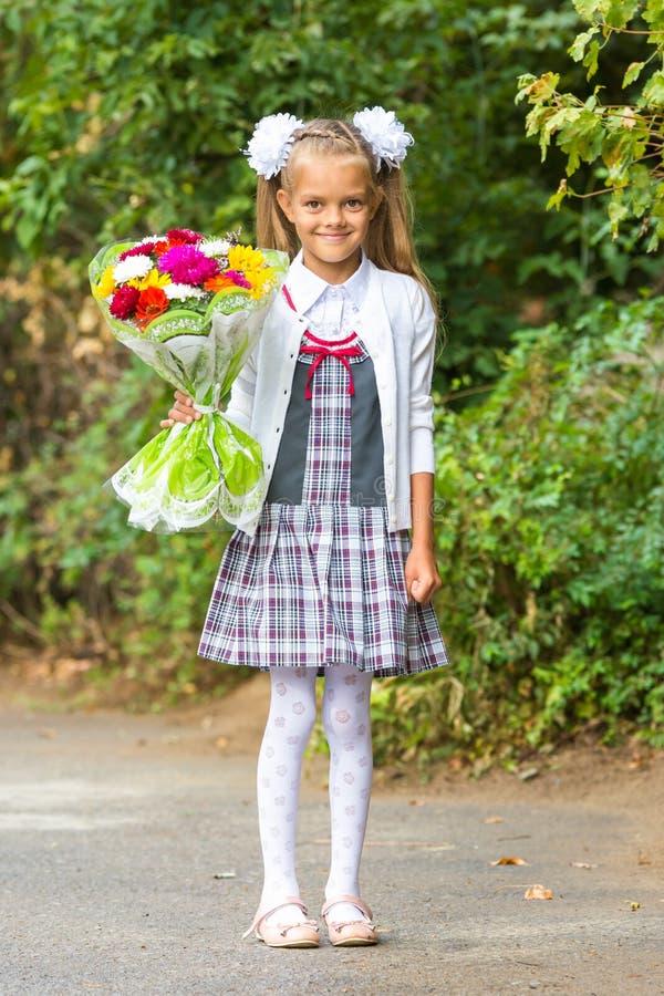 Portret van zevenjarig eerstegraadsmeisje met een boeket van bloemen stock afbeelding