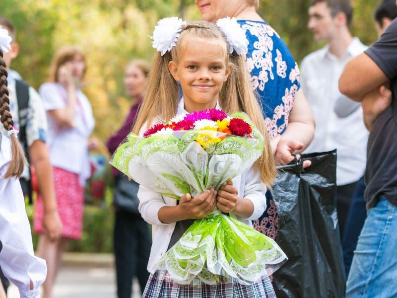 Portret van zevenjarige die middelbare schoolmeisjes in school 1 September, door een menigte van volwassenen wordt omringd stock fotografie