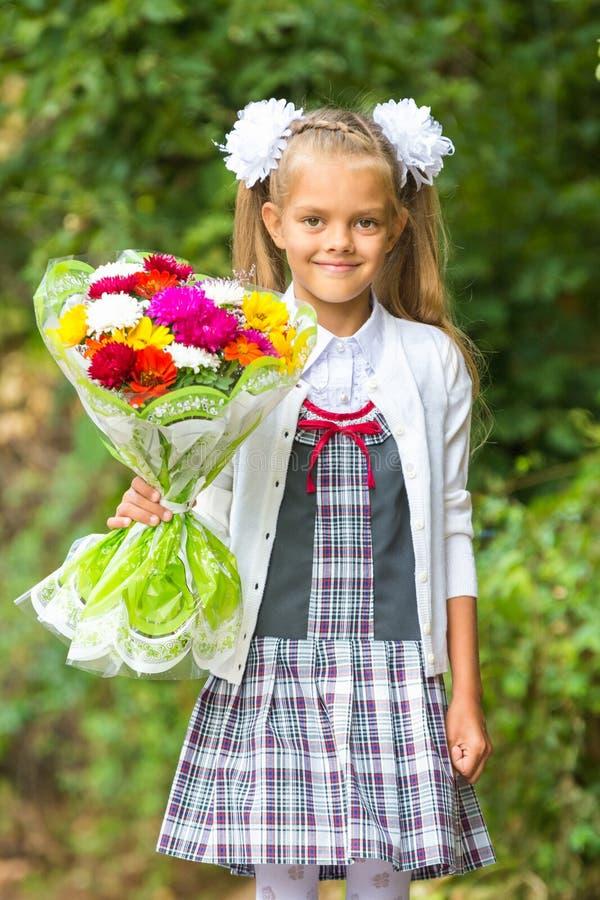 Portret van zevenjarige eerstegraadsmeisjes die naar school op 1 binnen gaan September stock afbeelding