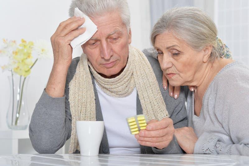 Portret van ziek hoger paar met pillen thuis royalty-vrije stock afbeelding