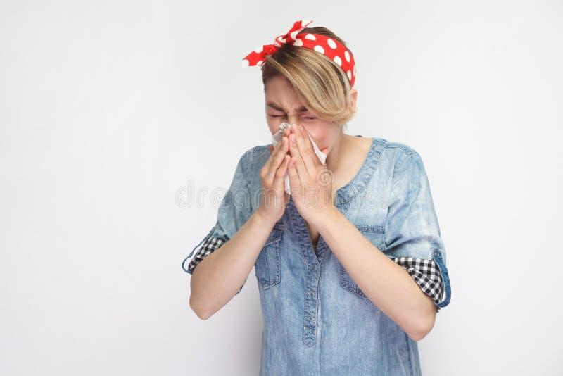 Portret van zieke jonge vrouw in toevallig blauw denimoverhemd met rode hoofdband die zich met weefsel bevinden en haar lopende n royalty-vrije stock fotografie