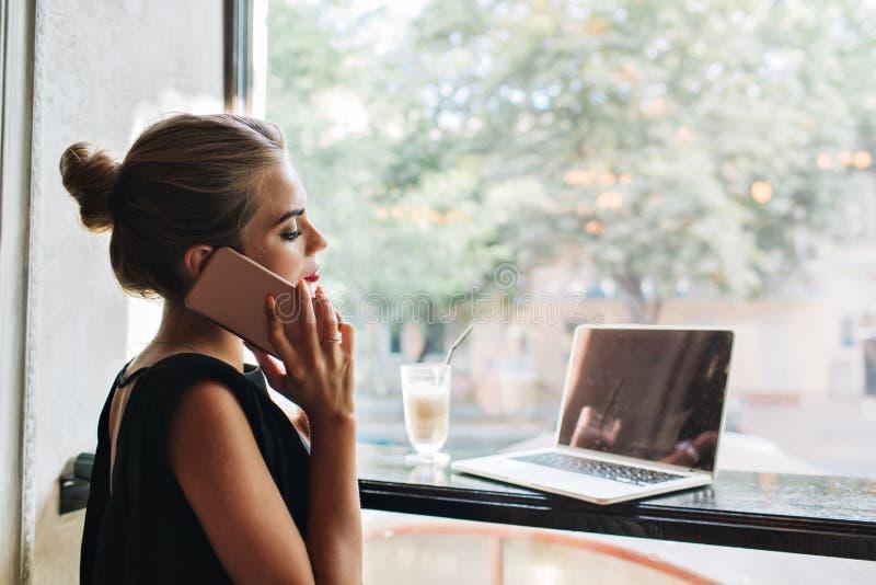 Portret van zij mooie vrouw in zwarte kleding in cafetaria Zij spreekt op telefoon, kijkend op laptop stock fotografie