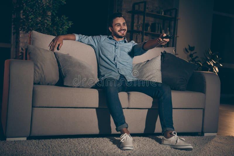 Portret van zijn mooie, vrolijke, vrolijke brunet-man die op divan zit te kijken terwijl hij tv-programma van tv-show wisselt royalty-vrije stock foto's