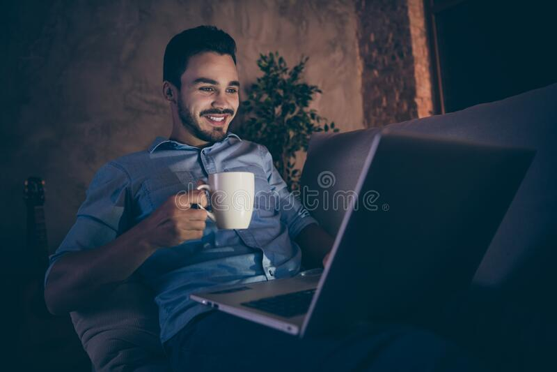 Portret van zijn mooie, zelfverzekerde, vrolijke, vrolijke brunet-man die laat op de divan zit met een laptop royalty-vrije stock foto