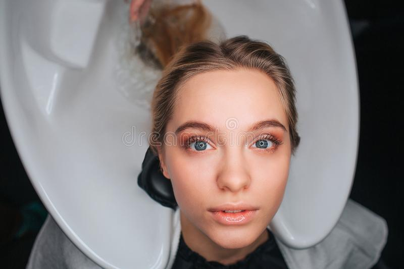 Portret van zitting van de blonde de mooie jonge vrouw op de witte gootsteen van de haarwas en wachten voor een kapper Washaar bi stock foto