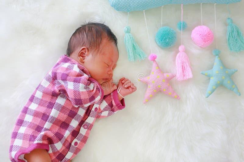 Portret van zoete de jongensslaap van de dromen pasgeboren baby op witte bontachtergrond met zachte mobiele stof stock afbeeldingen