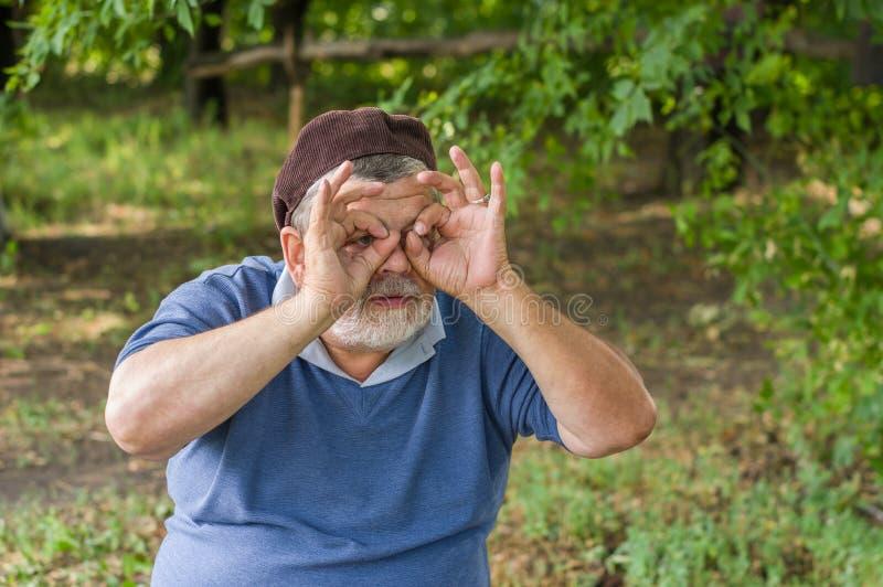 Portret van zonderling hoger makend gebaar als het kijken door binoculair royalty-vrije stock foto