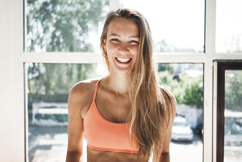 Portret van zonnebrand het geschikte vrouw dragen sportwear in zonnige witte gymnastiek royalty-vrije stock fotografie
