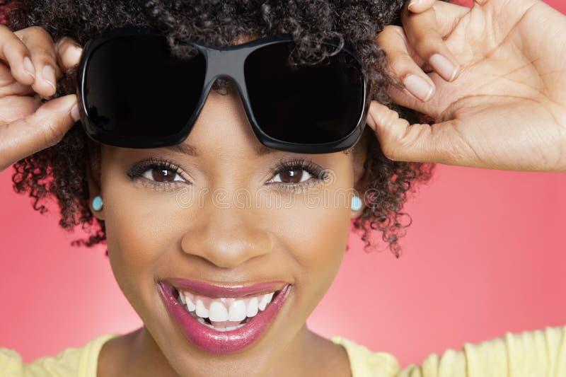 Portret van zonnebril van een de vrolijke Afrikaanse Amerikaanse vrouwenholding over gekleurde achtergrond royalty-vrije stock foto