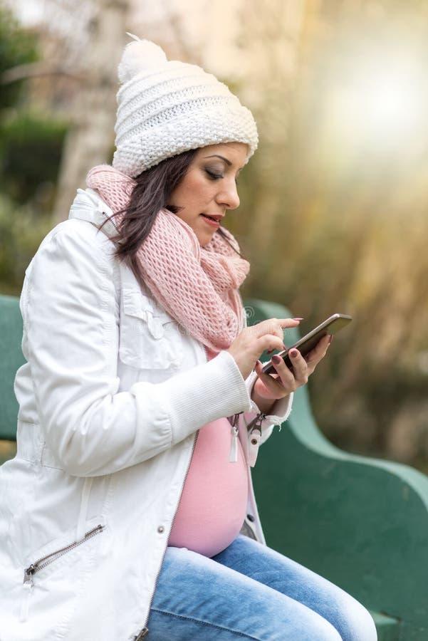 Portret van zwangere jonge vrouwenzitting op een bank en het gebruiken van haar mobil telefoon, lichteffect stock fotografie