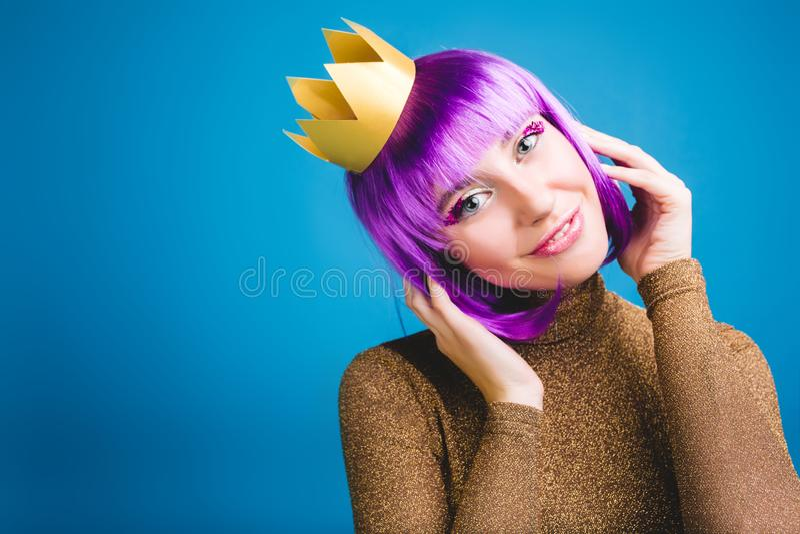 Portret vrolijke verbazende jonge vrouw met besnoeiings purper haar, gouden kroon, luxekleding op blauwe achtergrond celebrating royalty-vrije stock afbeeldingen