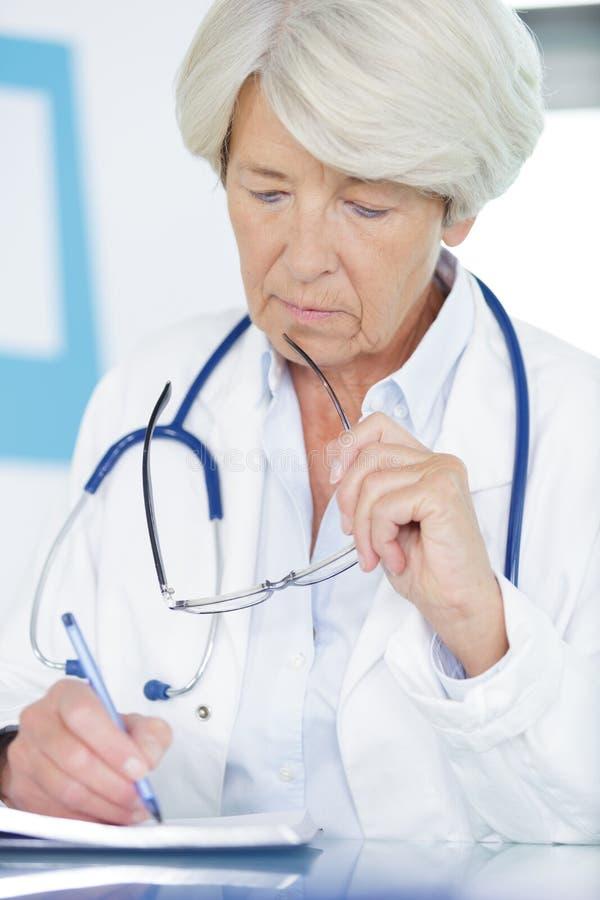 Portret vrouwelijke arts die op klembord schrijven stock foto